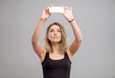 Mujer joven que toma imágenes a través de su teléfono Imagenes de archivo