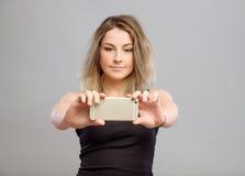 Mujer joven que toma imágenes a través de su teléfono Foto de archivo