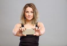Mujer joven que toma imágenes a través de su teléfono Fotografía de archivo