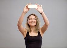 Mujer joven que toma imágenes a través de su teléfono Fotos de archivo