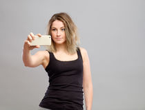 Mujer joven que toma imágenes a través de su teléfono Fotografía de archivo libre de regalías