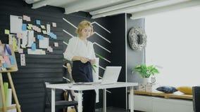 Mujer joven que toma la etiqueta engomada de un tablero y que se sienta en el escritorio metrajes