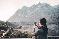 Mujer joven que toma la foto con su teléfono del Mountain View hermoso Fotos de archivo libres de regalías