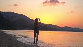 Mujer joven que toma la foto de la puesta del sol hermosa con el teléfono móvil que se coloca en la playa en la cámara lenta 1920 almacen de video
