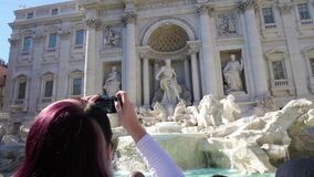 Mujer joven que toma la foto de sorprender la fuente del palacio y del Trevi de Poli en Roma metrajes