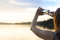 Mujer joven que toma la foto de una puesta del sol hermosa con el teléfono elegante Imagen de archivo libre de regalías