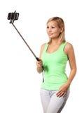 Mujer joven que toma la foto del selfie con el palillo aislado Foto de archivo libre de regalías
