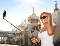 Mujer joven que toma la foto del selfie con el palillo delante de Taj Mahal Imágenes de archivo libres de regalías