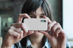 Mujer joven que toma la foto por la cámara móvil imagen de archivo libre de regalías