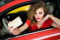 Mujer joven que toma la imagen del selfie con la cámara elegante del teléfono en coche Fotos de archivo