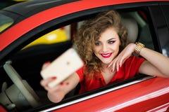 Mujer joven que toma la imagen del selfie con la cámara elegante del teléfono en coche Fotografía de archivo libre de regalías