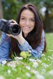 Mujer joven que toma la imagen que miente en hierba imagenes de archivo