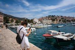 Mujer joven que toma las fotos de la bahía del mar fotografía de archivo