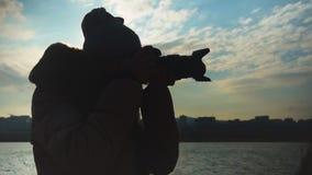 Mujer joven que toma las imágenes de la puesta del sol en el fondo del mar, de la ciudad y del cielo metrajes