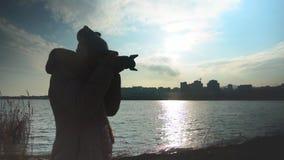 Mujer joven que toma las imágenes de la puesta del sol en el fondo del mar, de la ciudad y del cielo almacen de metraje de vídeo