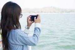 Mujer joven que toma paisaje de la foto mientras que se coloca en el barco o delantero Imagen de archivo