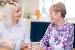 Mujer joven que toma tiempo para visitar al vecino femenino mayor y para hablar fotos de archivo libres de regalías