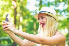 Mujer joven que toma un selfie afuera Foto de archivo