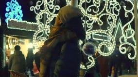 Mujer joven que toma un selfie con el teléfono elegante en el mercado de la Navidad almacen de metraje de vídeo