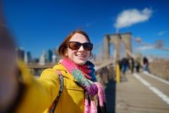Mujer joven que toma un selfie en el puente de Brooklyn Fotos de archivo
