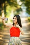 Mujer joven que toma un Selfie en parque Fotos de archivo