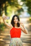 Mujer joven que toma un Selfie en parque Imagen de archivo libre de regalías