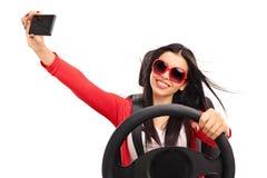 Mujer joven que toma un selfie mientras que conduce un coche Fotos de archivo libres de regalías