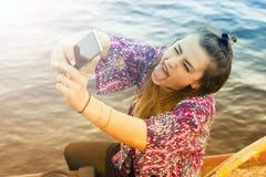 Mujer joven que toma un selfie y que saca su lengua Fotografía de archivo