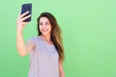 Mujer joven que toma un selfie y que sonríe contra fondo verde Imagen de archivo