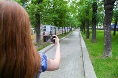 Mujer joven que toma una foto con su teléfono Imagen de archivo