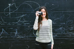 Mujer joven que toma una foto con una cámara vieja Foto de archivo