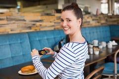 Mujer joven que toma una foto de su almuerzo Imagenes de archivo