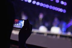 Mujer joven que toma una fotografía con su teléfono elegante en un concierto interior, sobre la opinión del hombro Fotografía de archivo libre de regalías