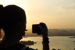 Mujer joven que toma una imagen de la puesta del sol hermosa en Udaipur fotos de archivo