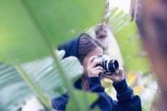 Mujer joven que toma una imagen en un bosque Foto de archivo
