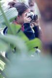 Mujer joven que toma una imagen en una área arbolada Foto de archivo libre de regalías
