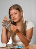 Mujer joven que toma una píldora Fotografía de archivo libre de regalías