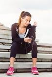 Mujer joven que toma una rotura del ejercicio afuera con el teléfono móvil Foto de archivo