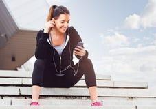 Mujer joven que toma una rotura del ejercicio afuera con el teléfono móvil Imagenes de archivo