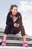 Mujer joven que toma una rotura del ejercicio afuera con el teléfono móvil Foto de archivo libre de regalías