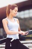 Mujer joven que toma una rotura del ejercicio afuera con el teléfono móvil Imagen de archivo libre de regalías