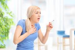 Mujer joven que tose de un cigarrillo Fotografía de archivo libre de regalías