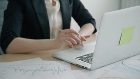 Mujer joven que trabaja con el ordenador portátil, escribiendo en la tabla en oficina moderna metrajes