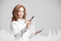 Mujer joven que trabaja con la carta del gráfico Tecnologías futuras para el negocio, concepto del mercado de acción Fotos de archivo