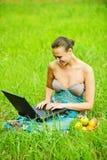 Mujer joven que trabaja con la computadora portátil Imágenes de archivo libres de regalías