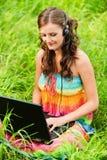 Mujer joven que trabaja con la computadora portátil Fotos de archivo