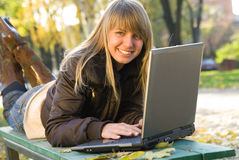 Mujer joven que trabaja con la computadora portátil en parque de la ciudad Fotos de archivo