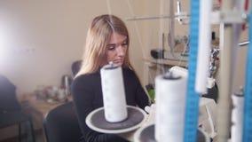 Mujer joven que trabaja con la máquina de coser en fábrica Metro en el marco metrajes