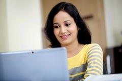 Mujer joven que trabaja con la tableta Fotografía de archivo libre de regalías