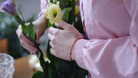 Mujer joven que trabaja con las flores amarillas y púrpuras primer imagen de archivo